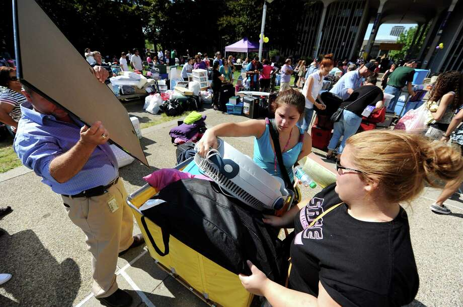 Freshman Bianca Hotte, 18, of Troy, center, receives help from her sister Theresa, 19, right, on moving-in day on Wednesday, Aug. 22, 2012, University at Albany in Albany, N.Y. (Cindy Schultz / Times Union) Photo: Cindy Schultz / 00018846A