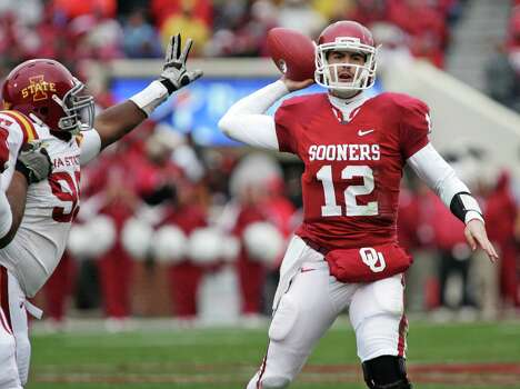 Quarterback Landry Jones #12 of the Oklahoma Sooners looks to throw under pressure in the first half on November 26, 2011 at Gaylord Family-Oklahoma Memorial Stadium in Norman, Okla. Photo: Brett Deering, Getty Images / 2011 Getty Images