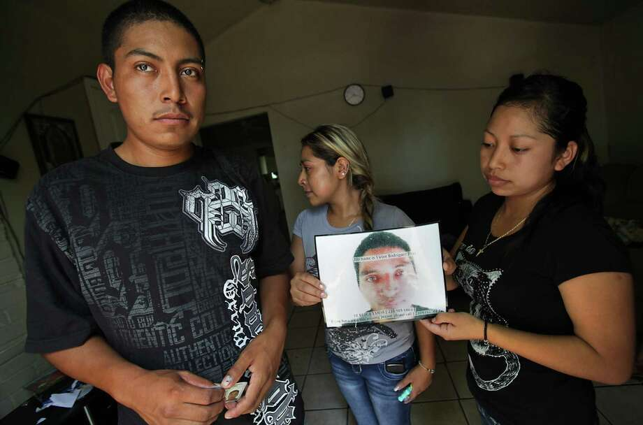 Nereo Diaz, 23, left to right, Elda Diaz, 24, and Luci Diaz, 21, siblings of Victor Diaz, whose body was found in the Pearl Brewery smokestack, hold a photo of him in at Nereo's house.  The family is from Chiapas. Wednesday, August 22, 2012. Photo: BOB OWEN, San Antonio Express-News / © 2012 San Antonio Express-News