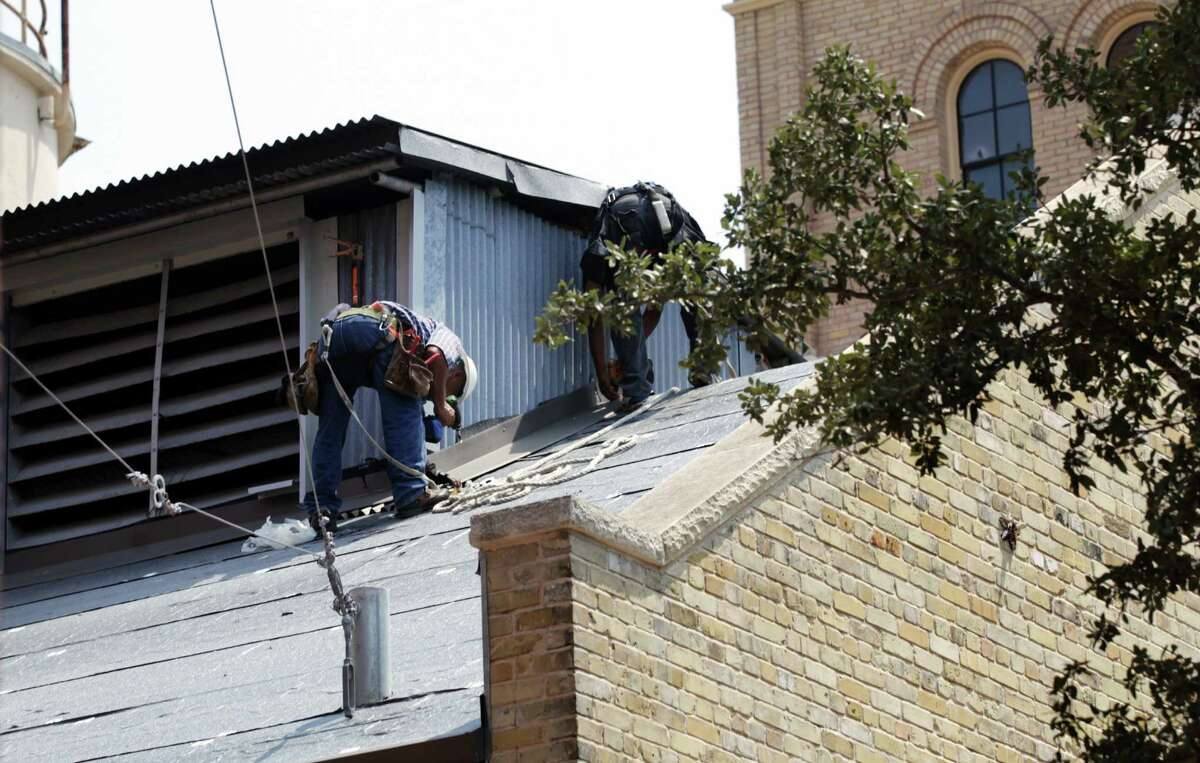 Roofing work continues at the Pearl Brewery. Victor Diaz, whose body is believed to be the one found inside the brewery's old smokestack, was on his first day of work there.