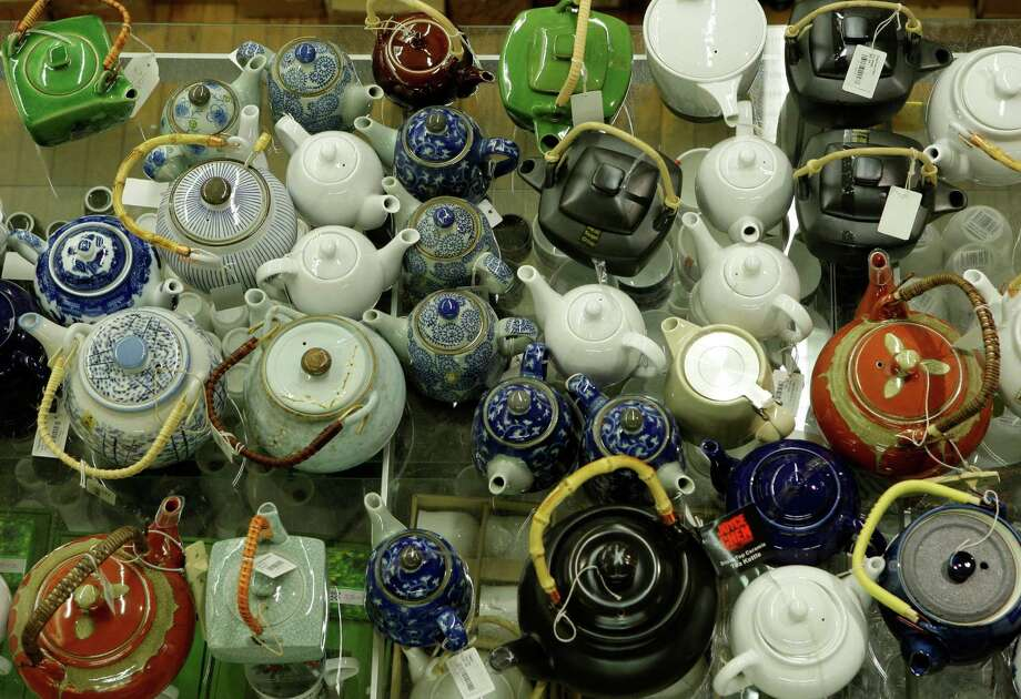 A colorful array of teapots crowd a shelf at Pearl River Mart near Chinatown in New York, Tuesday, Dec. 30, 2008. The store is an emporium for Asian goods ranging from paper lanterns to silk purses and musical instruments. (AP Photo/Kathy Willens) Photo: Kathy Willens / AP
