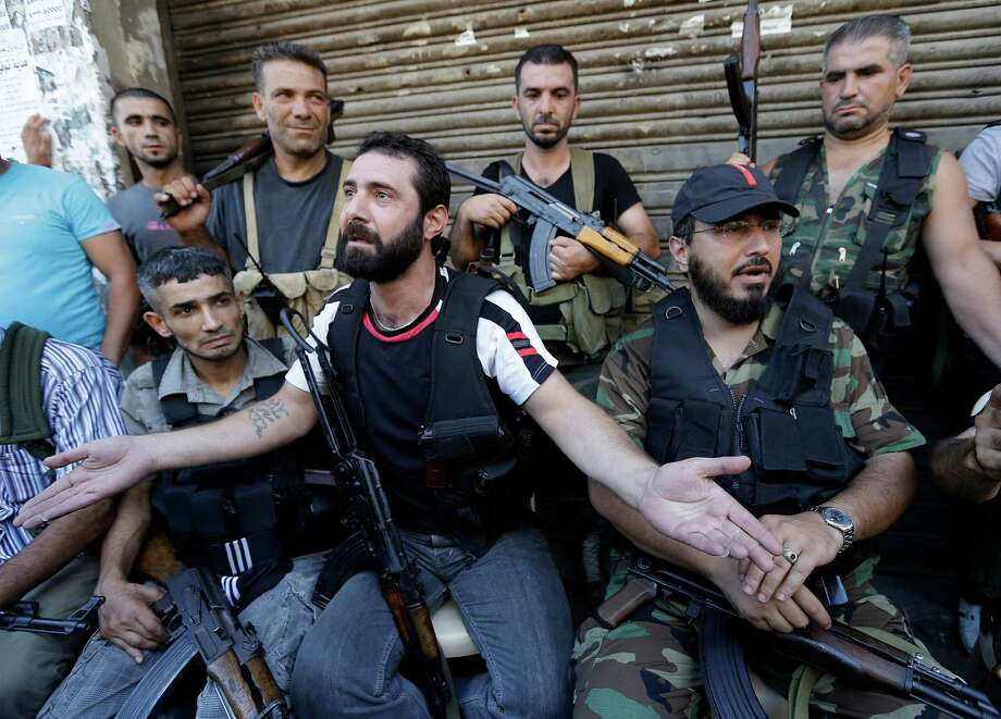 Sunni Muslim fighters, such as these in the port city of Tripoli, might find the chaos in Lebanon makes it easier to supply anti-Assad rebels in Syria. The unrest in Syria might bring instability to Lebanon as well. Photo: Hussein Malla / AP