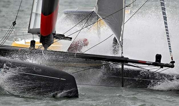 A sailor on the Artemis Racing Red boat is hit by a wave while competing during the America's Cup World Series. Photo: Beck Diefenbach, Special To The Chronicle