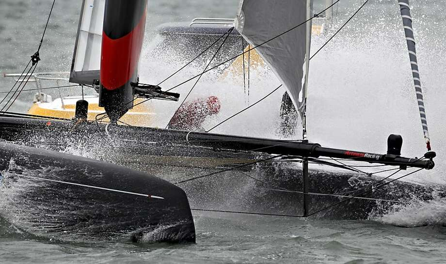 A sailor on the Artemis Racing Red boat is hit by a wave while competing during the America's Cup World Series on Wednesday, August 22, 2012 in San Francisco, Calif. Photo: Beck Diefenbach, Special To The Chronicle