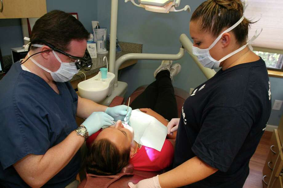 Old Greenwich Dental Associates dentist Dr. Greg Busch, left, works on Maggie Zalewska of Stratford, as dental assistant Melissa Rippel looks on, during a free dental day event called Dentistry from the Heart Friday, August 17, 2012. Photo: David Ames, Greenwich Time / Greenwich Time