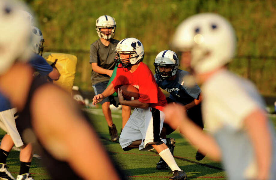 James Coppola, center, runs the ball during Immaculate High School football practice in Danbury on Wednesday, Aug. 22, 2012. Photo: Jason Rearick / The News-Times