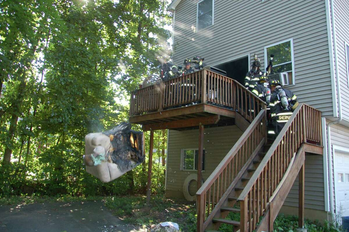 Danbury firefighters throw a couch that was burned in a fire on James Street off the back deck of the residence Wednesday afternoon.