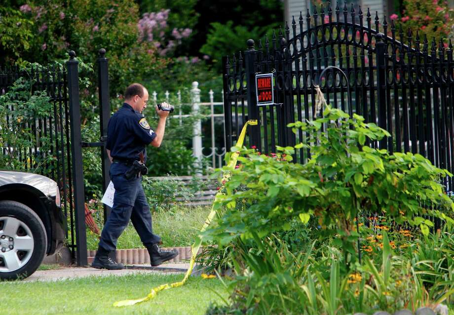 An HPD crime scene officer investigates the scene of a shooting at a home on Beggs near Cavalcade. A man and his girlfriend were shot after they refused to open the back door to a man dressed as a security guard. Photo: Mayra Beltran / © 2012 Houston Chronicle
