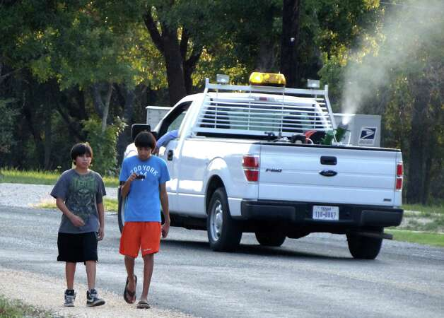 Daniel Hinojosa, left, and Jose Segura walk along Hickory Way in South Bexar County as a vector control truck drives by, fogging the area in an effort to eradicate mosquitos on Wednesday, Aug. 22, 2012. The county recently recorded its first West Nile virus death. Photo: Billy Calzada, San Antonio Express-News / © San Antonio Express-News