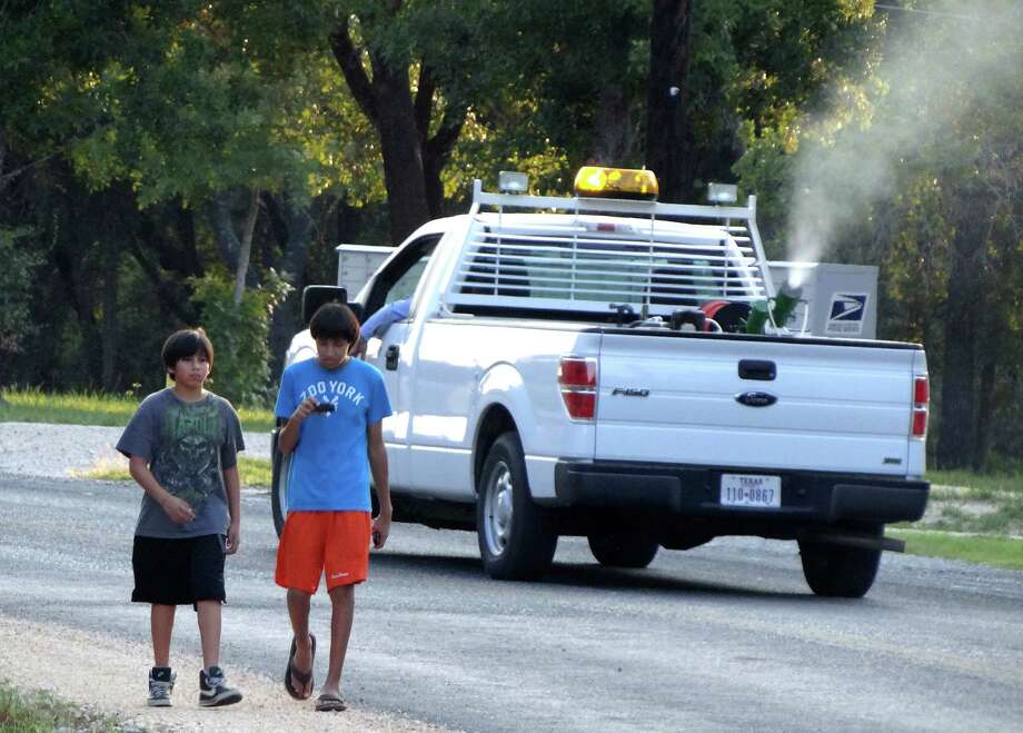 Daniel Hinojosa (left) and Jose Segura walk along Hickory Way in southern Bexar County as a vector control truck drives by, spraying in an effort to eradicate mosquitoes. Photo: Billy Calzada, San Antonio Express-News / © San Antonio Express-News