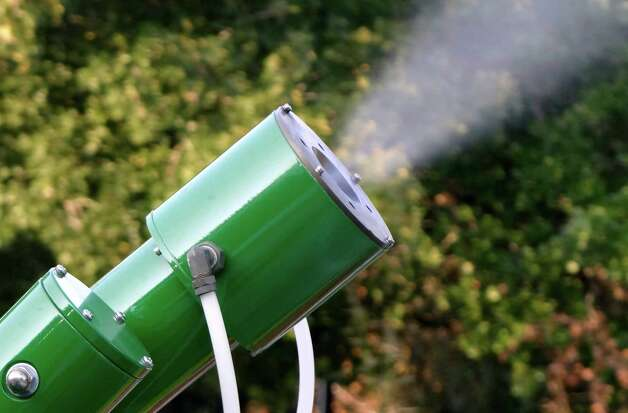 A nozzle on a truck sprays a fog to eradicate mosquitos along Hickory  Way in South Bexar County on Aug. 22, 2012. The county recently recorded its first West Nile virus death. Photo: Billy Calzada, San Antonio Express-News / © San Antonio Express-News