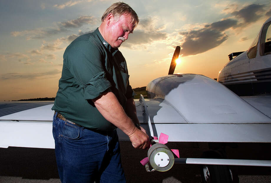 Malcom Williams, the chief pilot for Vector Disease Control, Inc., makes final checks at Hooks Airport on Wednesday before conducting aerial mosquito-control operations in west and north Harris County. Photo: Cody Duty / © 2011 Houston Chronicle