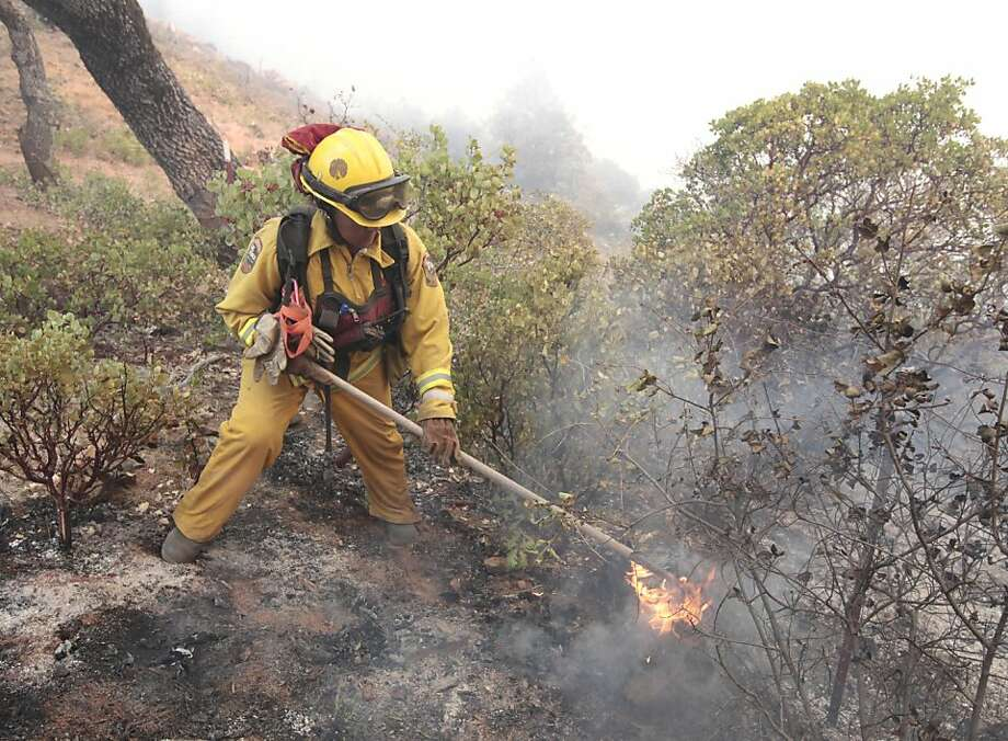 Firefighter Denise Alcorn puts out flames on a log burning at the Ponderosa Fire, near Paynes Creek, Calif., Wednesday, Aug. 22, 2012.  The Ponderosa Fire, which has scorched about 38 square miles, was 50 percent contained Wednesday morning, according to the California Department of Forestry and Fire Protection. No lives have been lost in the Ponderosa Fire. Photo: Rich Pedroncelli, Associated Press