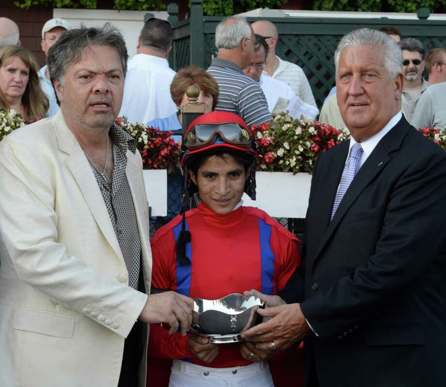 Mayor Jerry Jennings, right present the trophy to James Riccio, left the winning owner of Willy Beamin the winner of 35th running of The Albany, The Big Apple Triple - Third Leg to James Riccio at the Saratoga Race Course in Saratoga Springs, N.Y. Aug 22, 2012.  With Riccio and Jennings is the winning jockey Alan Garcia.  (Skip Dickstein/Times Union) Photo: Skip Dickstein