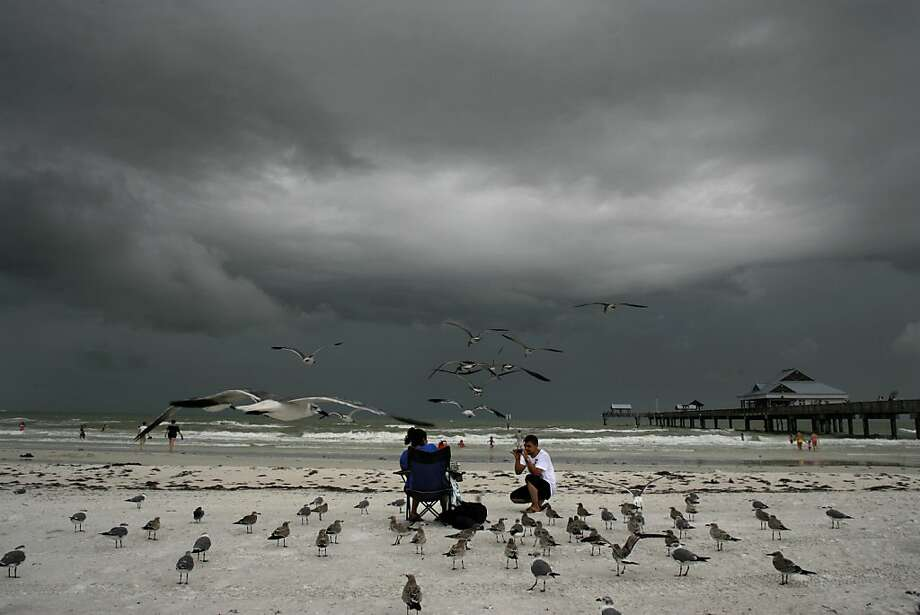 Hector Hernandez takes a photo of his wife Brenda Palatieos as a storm over the gulf rolls into Clearwater Beach, Florida, Wednesday afternoon on August 22, 2012. Photo: Jim Damaske, McClatchy-Tribune News Service