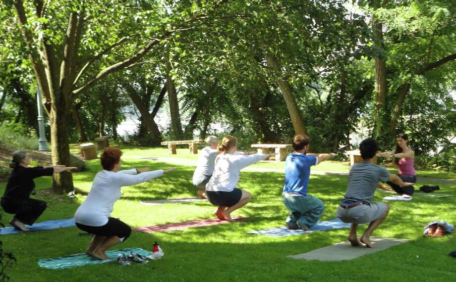 Sarah O'Donaghue, a yoga instructor and employee of the Westport Public Library, led a yoga lesson along the Saugatuck River on the library grounds Wednesday. The class was so popular that the library is considering offering the class once a week. Photo: Meg Barone / Westport News freelance