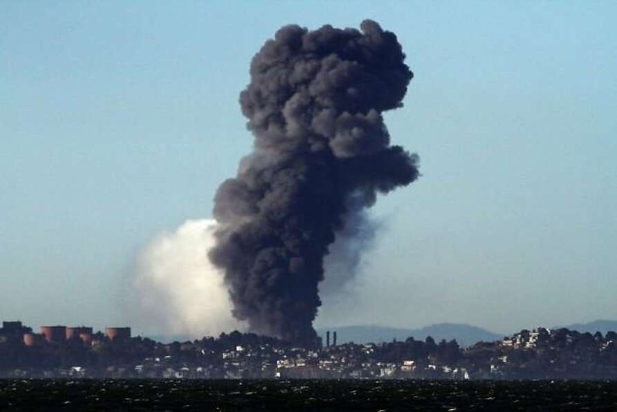 A cloud of black smoke billows upward after the vapor cloud ignited, starting a blaze at the oil pla