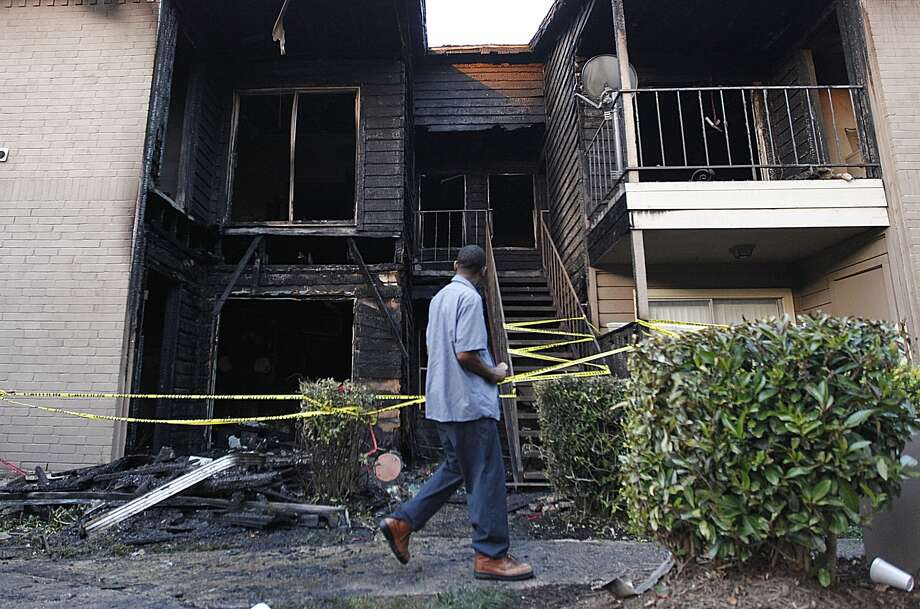 Residents walk by the destroyed apartment unit where two people were injured during a two alarm fire at South Point apartment complex. ( Mayra Beltran / Houston Chronicle )
