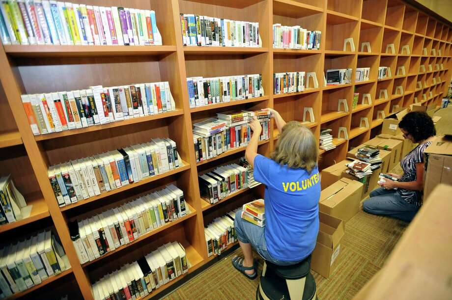 Peggy Rhame, left, and Sheila Metreyeon, right, both volunteers with the library, fill the shelves as staff and volunteers alike ready the library for the upcoming opening.  The RC Miller Library, which has been closed due to renovation, is slated to open next Monday, August 27, 2012.  Dave Ryan/The Enterprise Photo: Dave Ryan