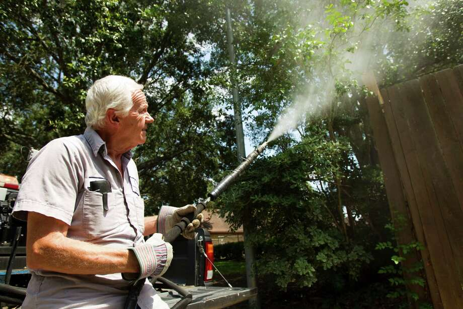 Paul Culbertson, of Montgomery County Pct. 3 Mosquito Abatement, sprays a stand of trees to fight mosquitos Wednesday, June 6, 2012, in The Woodlands. Recent testing in South Montgomery County revealed the presence of West Nile virus. ( Brett Coomer / Houston Chronicle ) Photo: Brett Coomer, Houston Chronicle / © 2012 Houston Chronicle