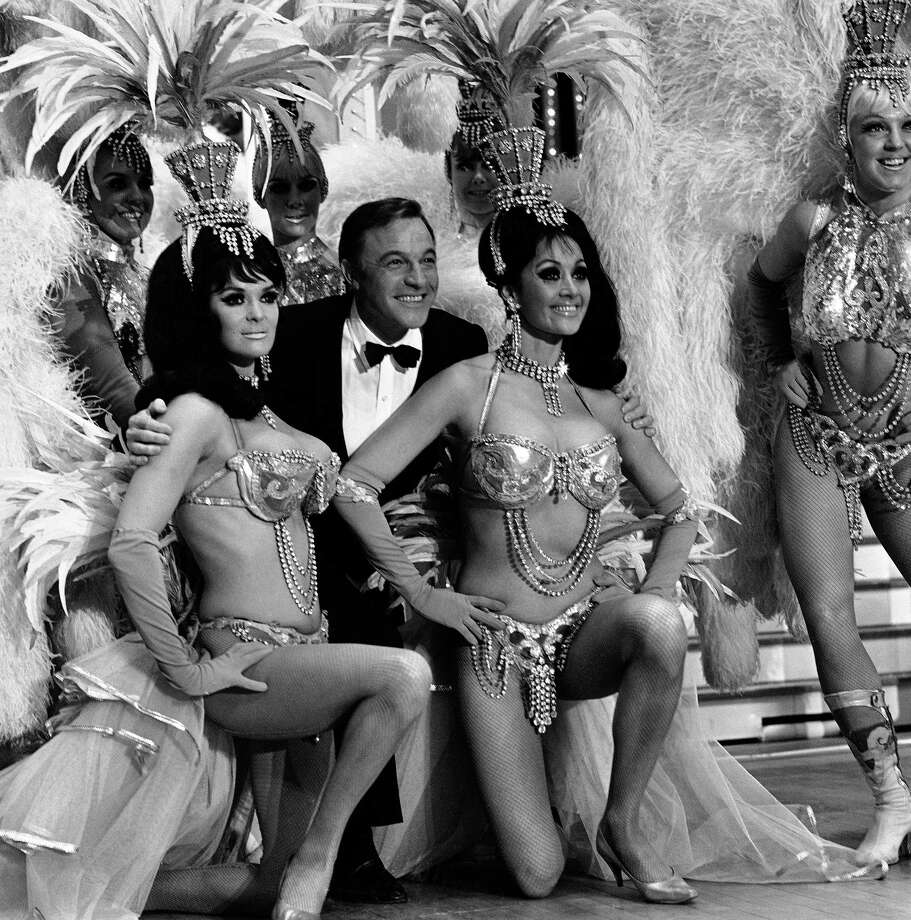 "Actor Gene Kelly is framed by Felicia Atkins, left, and Joyce Grayson, members of the famed Folies Bergere, during rehearsal for his TV special, ""Gene Kelly's Wonderful World of Girls,"" at the Hotel Tropicana in Las Vegas, April 14, 1959. Photo: AP"
