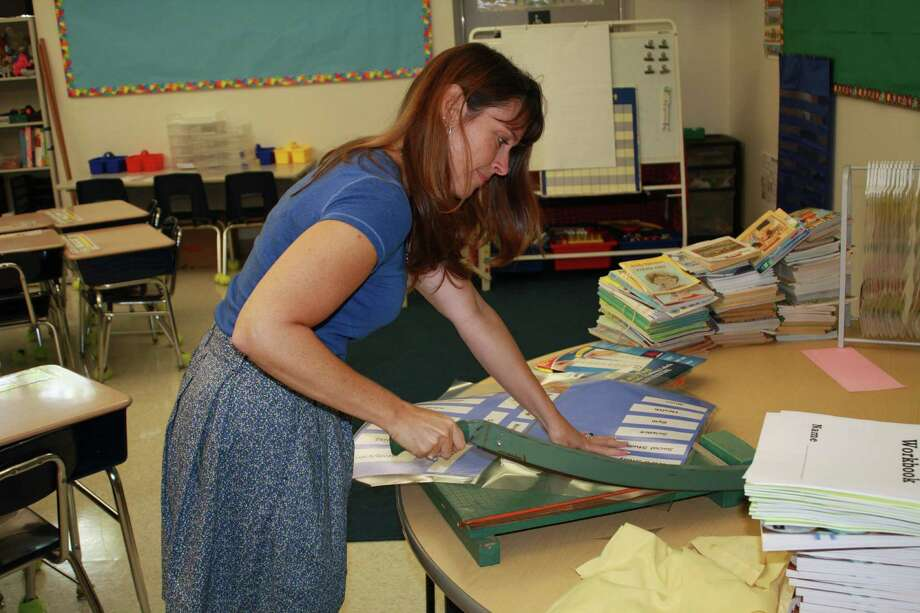 Gail Smith, a third-grade teacher at Tokeneke Elementary School in Darien, decorates her classroom Wednesday, Aug. 22, 2012, before the start of school. Photo by Megan Davis Photo: Contributed Photo