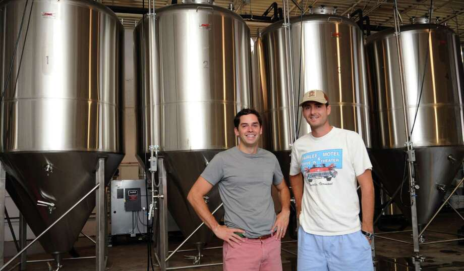 Founder and Chief Beer Philosopher Conor Horrigan, left, and Jordan Giles, Chief Beer Organizer, right, pose for a photo in front of fermentation tanks at Half Full Brewery in Stamford on Thursday, August 23. 2012. Photo: Lindsay Niegelberg / Stamford Advocate