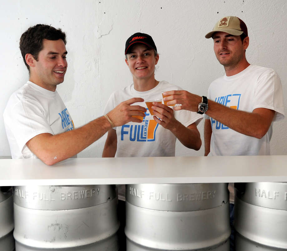 Founder and Chief Beer Philosopher Conor Horrigan, left, Jennifer Muckerman, Chief Beer Artist, center, and Jordan Giles, Chief Beer Organizer, right, pose for a photo at Half Full Brewery in Stamford on Thursday, August 23. 2012. Photo: Lindsay Niegelberg / Stamford Advocate
