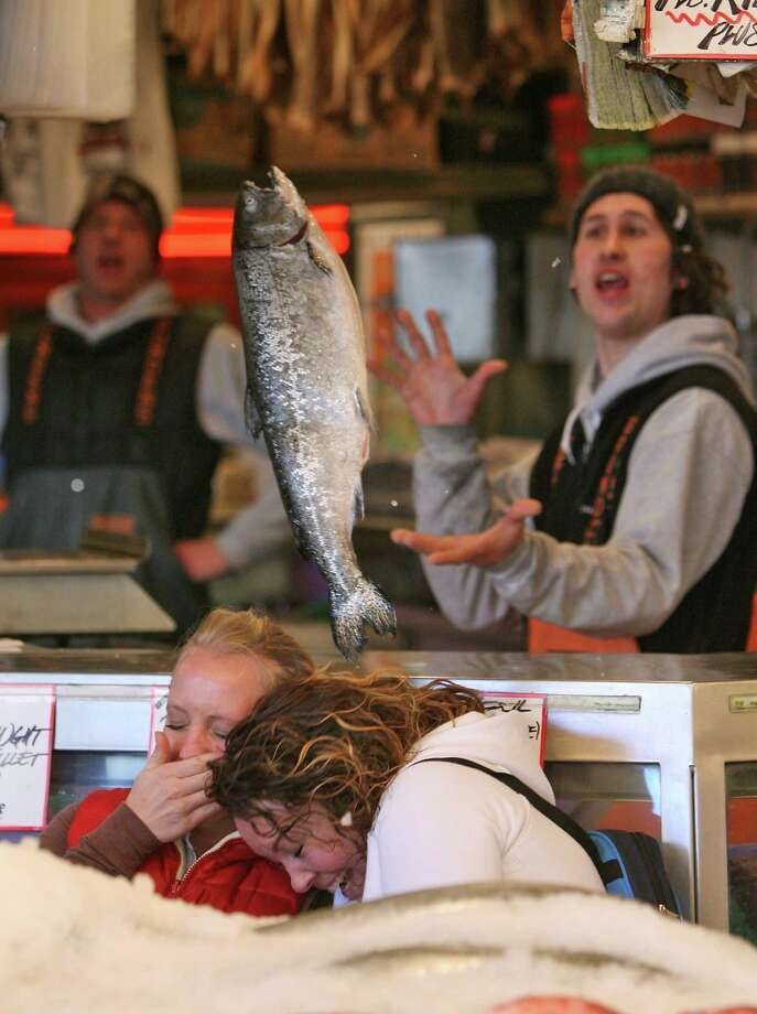 Flying fish: The throwing fishmongers at Pike Place Fish Market always draw a crowd. The star changes each day or so, when a new fish gets tossed around. (Photo by Mike Urban/Seattle Post-Intelligencer) Photo: Mike Urban, As Credited / Seattle Post-Intelligencer