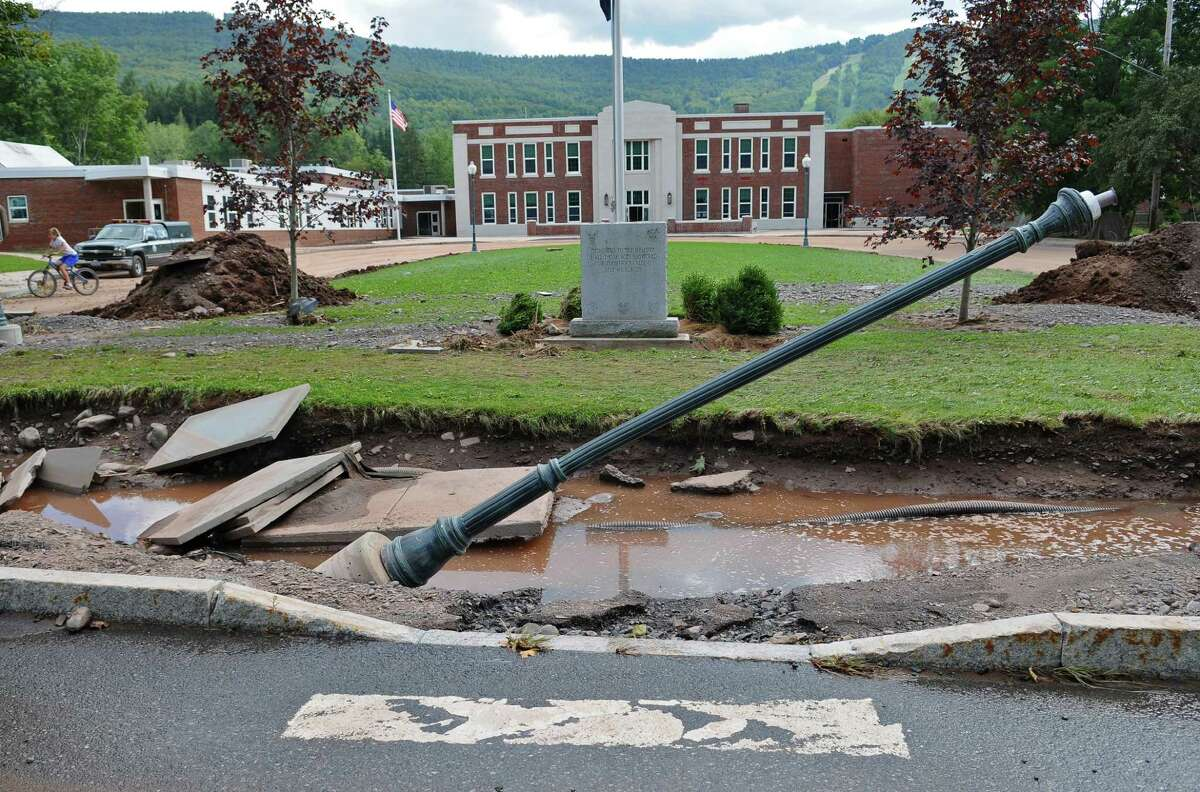 Seventh grader Augustus Shuster, left, rides his bike past the front of the Windham Ashland Jewett Central School, damaged as a result of Tropical Storm Irene, on Wednesday Aug. 31, 2011, in Windham, NY. (Philip Kamrass / Times Union)