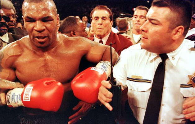 Mike Tyson (Left) is held back by police after his fight against Evander Holyfield for the WBA heavyweight championship at the MGM Grand Garden Arena in Las Vegas, NV, June 28. Holyfield won the fight on a disqualification at the end of the third round after Tyson bit Holyfield's ears. (JEFF HAYNES / AFP/Getty Images)