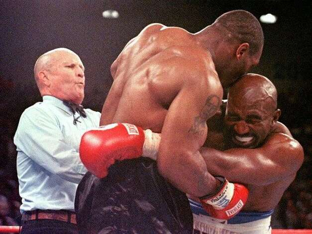 "(FILES): This 28 June 1997 file photo shows referee Lane Mills (L) stepping in as Evander Holyfield (R) reacts after Mike Tyson (C) bit his ear in the third round of their WBA Heavyweight Championship Fight at the MGM Grand Garden Arena in Las Vegas, NV.  A decade after his infamous ""Bite Fight"" victory over Mike, Holyfield still dreams of retaking boxing's heavyweight throne and considers most reigning champions ""beatable"". The 44-year-old US veteran will fight 41-year-old American Lou Savarese in a 10-round affair 30 June 2007 in El Paso, Texas, seeking the fourth victory in a row since making a comeback after being banished by New York officials following a loss.   AFP PHOTO/FILES/JEFF HAYNES (Photo credit should read JEFF HAYNES/AFP/Getty Images) (AFP/Getty Images)"