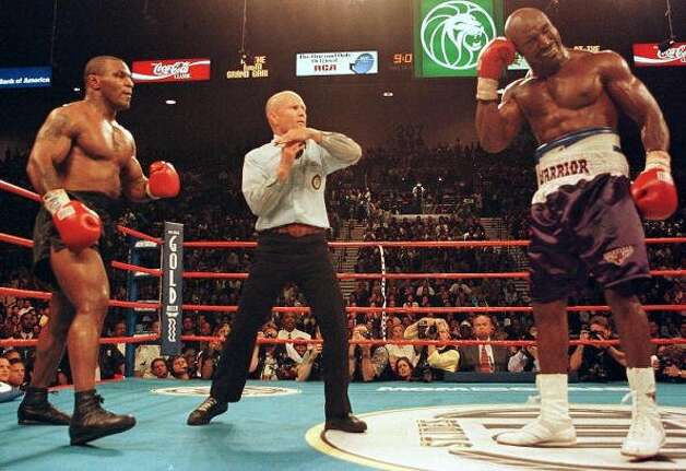 Referee Lane Mills (center) stops the fight in the third round as Evander Holyfield (Right) holds his ear, and Mike Tyson (Left) watches during their WBA heavyweight championship fight at the MGM Grand Garden Arena in Las Vegas, NV., June 28, 1997. Holyfield won the fight on a disqualification at the end of the third round after Tyson bit Holyfield's ears. (JEFF HAYNES / AFP/Getty Images)