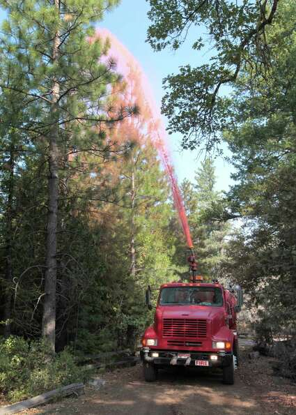 Fire retardant is sprayed on trees surrounding a home as a precaution, as the Ponderosa Fire nears M