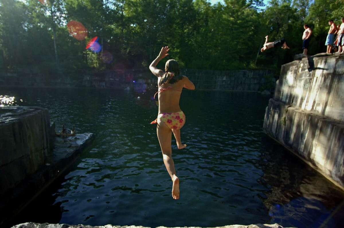A jumper leaps into the water at Dorset Quarry, a popular swimming hole at the site of the oldest marble quarry in the United States. 15-foot drops are an unobstructed path to the clear water below. Saturday, August 6, 2005. (Suzy Allman for The New York Times)