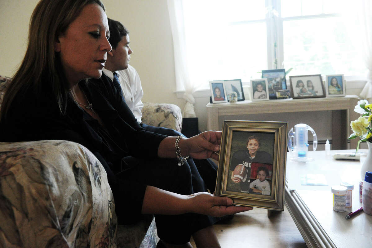 Deborah Bella sits with her son Brandon as she holds a photograph of her son, Kevin, in the family home in Stamford, Conn., August 23, 2012. Kevin Bella, 13, was killed in a motorcycle accident last week.