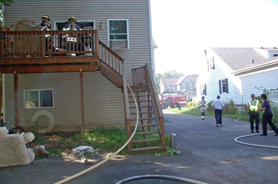 Firefighters clear out an apartment on James Street that was damaged by fire Wednesday, Aug. 22, 2012. Photo: Contributed Photo