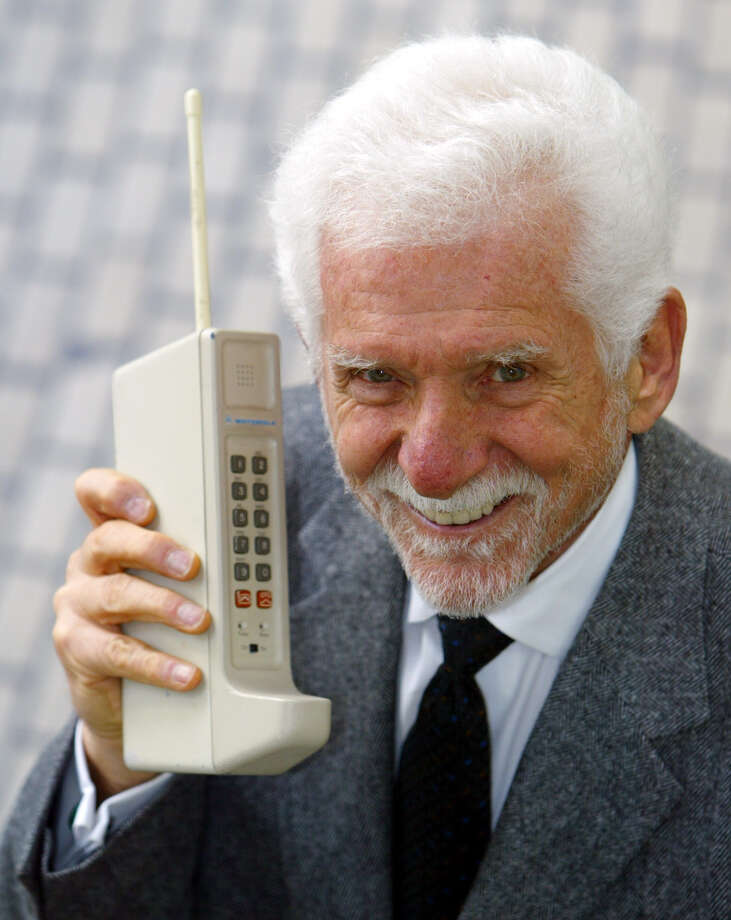 The Motorola DynaTAC was a 1973 prototype of the first handheld cellular telephone. Here's Martin Cooper, chairman and CEO of ArrayComm, holding one in San Francisco on April 2, 2003. Photo: ERIC RISBERG, AP / AP