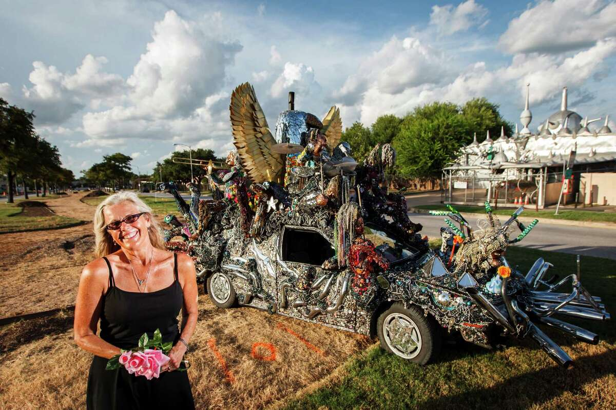 Rebecca Bass stands in front of her art car