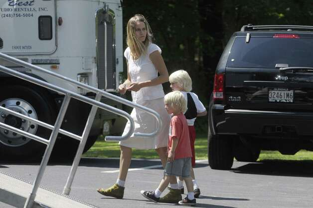 "Shannon Plumb, wife of director Derek Cianfrance, and the couple's two children, Walker, 7, behind, and Cody, 4, walk through a parking lot that is part of the Stanford Heights Fire Department in Schenectady on Wednesday, July 27, 2011.   A short time later the woman and the two children got into a van along with actor  Ryan Gosling.   The parking lot was being used by the crew of the movie ""The Place Beyond the Pines""  to work out of while filming was being done nearby.   (Paul Buckowski / Times Union) Photo: Paul Buckowski"