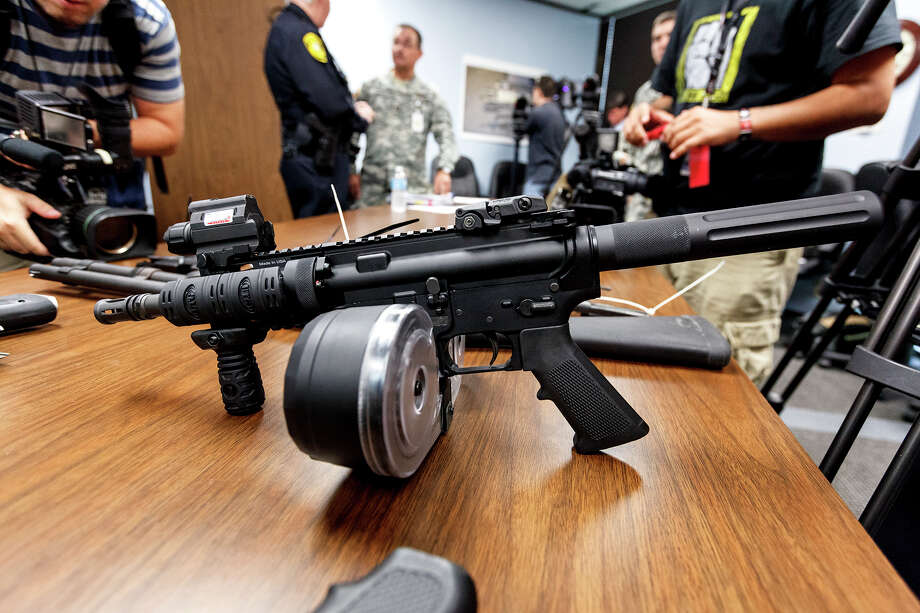 A modified AR-15 with  a 100-round magazine is displayed along with other weapons seized by law officers. Photo: MARVIN PFEIFFER, Marvin Pfeiffer/ Express-News / Express-News 2012