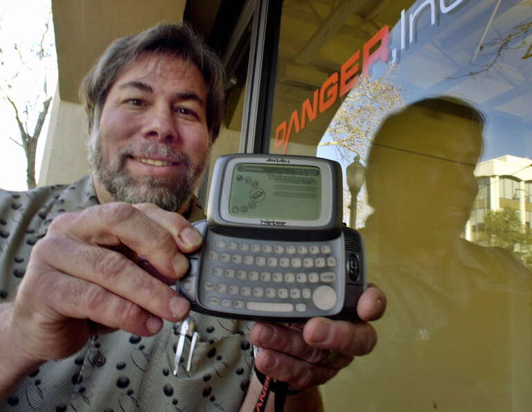 Apple co-founder Steve Wozniak, member of the board of directors of Danger Inc., holds up the compan