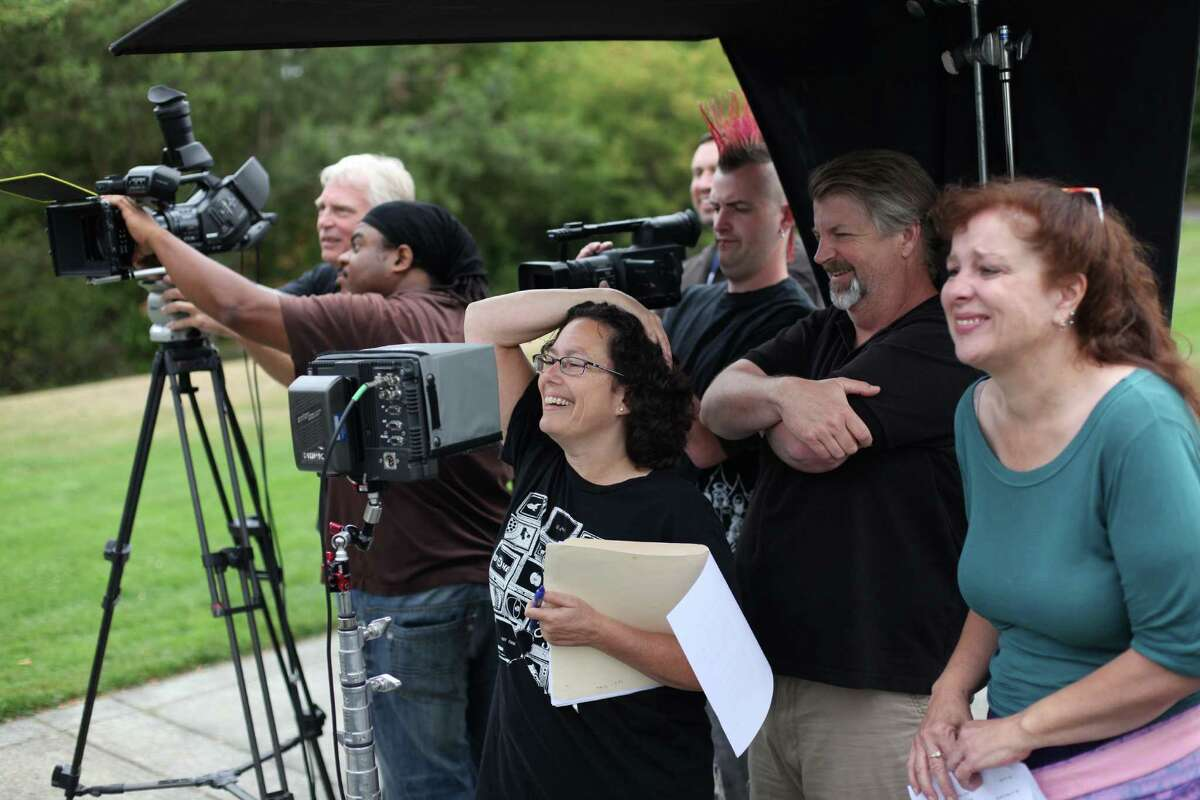 Producer Erren Gottlieb, center, watches on a monitor with other crew during a shoot for the new show