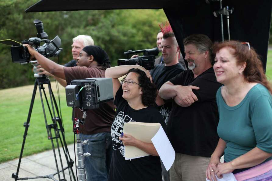 Producer Erren Gottlieb, center, watches on a monitor with other crew during a shoot for the new sho