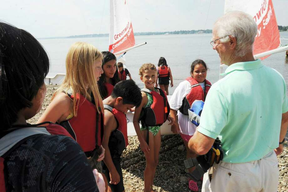 Tom O'Connell, founder of the Young Mariners Foundation of Greenwich, readies children for a sail in Greenwich Cove Thursday, Aug. 23, 2012. Eight members of the Boys & Girls Club of Greenwich participated in a summer sailing course offered through the Young Mariners Foundation of Greenwich at Old Greenwich Yacht Club. Photo: Helen Neafsey / Greenwich Time
