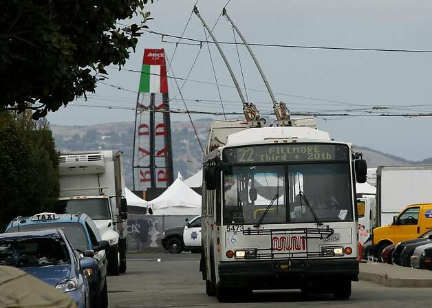 A 22-Fillmore Muni bus begins its southbound run while Italy's Luna Rossa Swordfish (background) competes in the America's Cup World Series boat races in San Francisco, Calif. on Thursday, Aug. 23, 2012.  The America's Cup is one of the number of events in San Francisco the weekend of Oct. 6-7 that will test Muni's service. Photo: Paul Chinn, The Chronicle