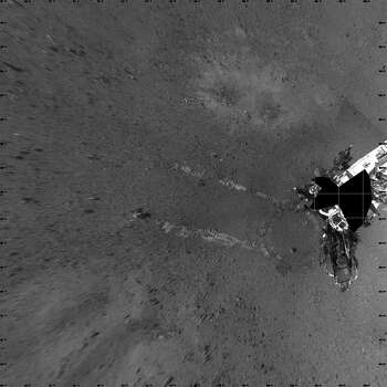 In this handout provided by NASA/JPL-Caltech, tracks from NASA's Curiosity Mars rover are seen from above in this composite image made from the Navigation camera  August 22, 2012 on Mars. According to NASA, the rover moved forward 15 feet, then rotated 120 degrees before reversing 8.2 feet during its first time moving. Photo: NASA, Getty Images / 2012 NASA