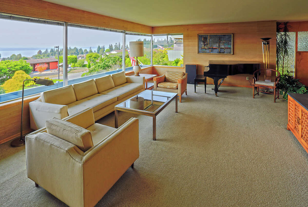 Living room of 12550 9th Ave. N.W.. The 4,330-square-foot mid-century modern house, was built in 1957, has four bedrooms, 2.25 bathrooms, wood walls, picture windows, period fixtures, a rec room, a covered patio, four fireplaces and a view deck on a 9,375-square-foot lot. It's listed for $750,000.