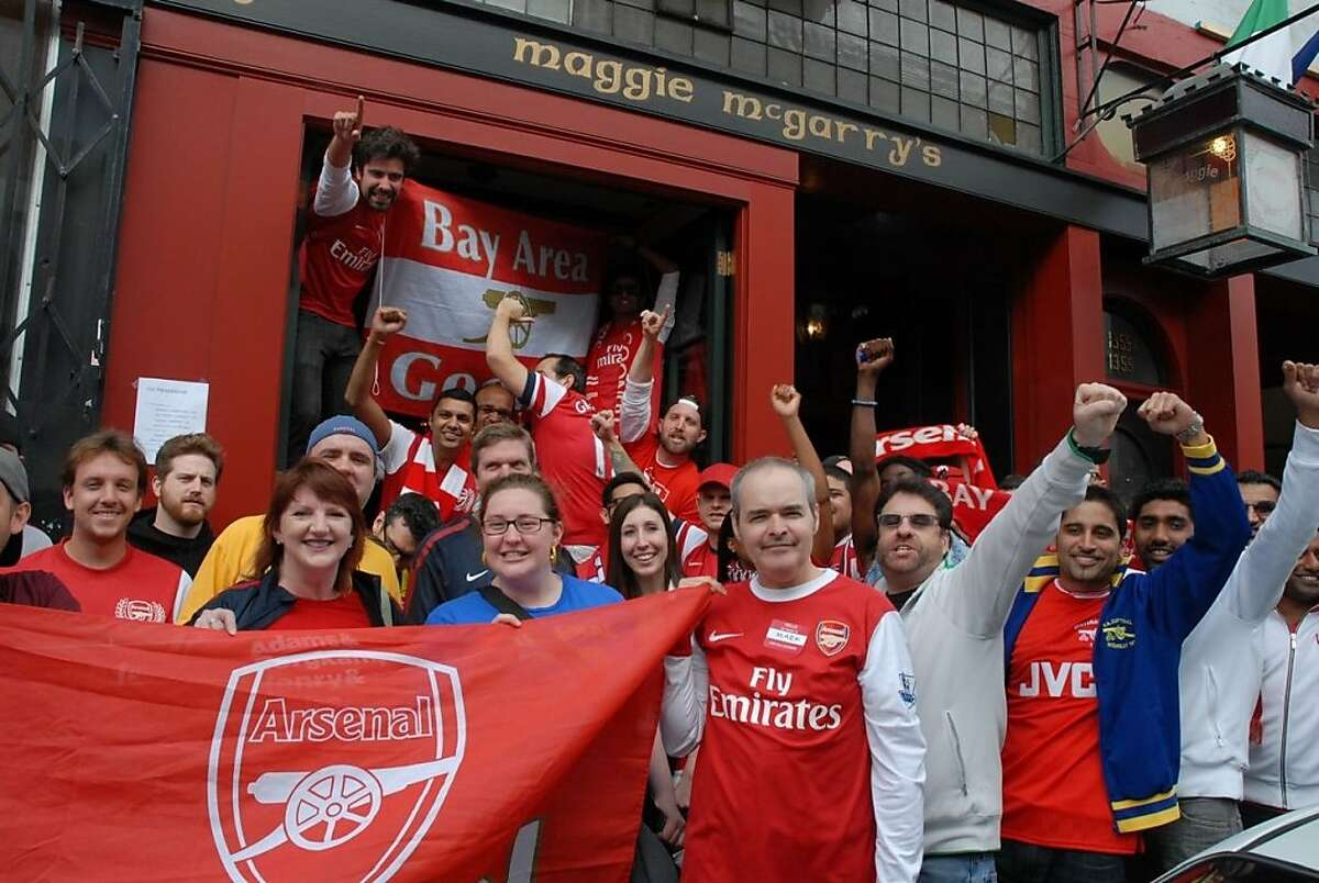 Gooners gather outside a bar while watching soccer early in the morning.