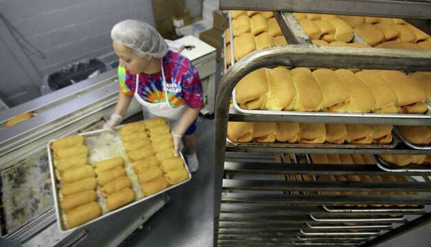 A worker at Chico's Bakery feeds Pepperoni Rolls in a wrapping machine in Morgantown, West Virginia. The affordable sandwich is a local favorite with sports fans. Thursday, Aug. 9, 2012. Photo: Bob Owen, Express-News / © 2012 San Antonio Express-News